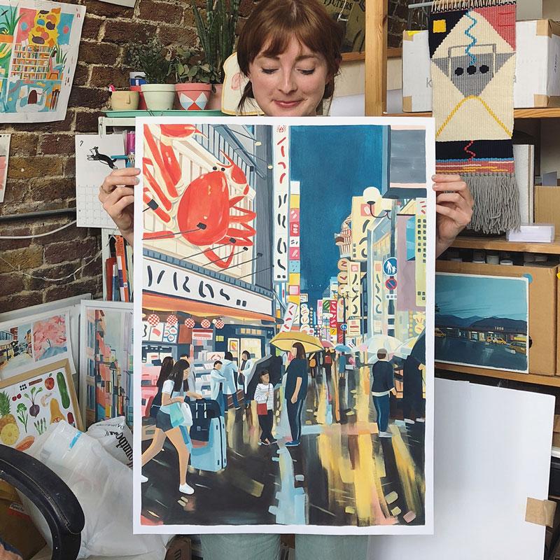 "Grace Helmer holding print with her artwork ""Osaka Dotonbori"""